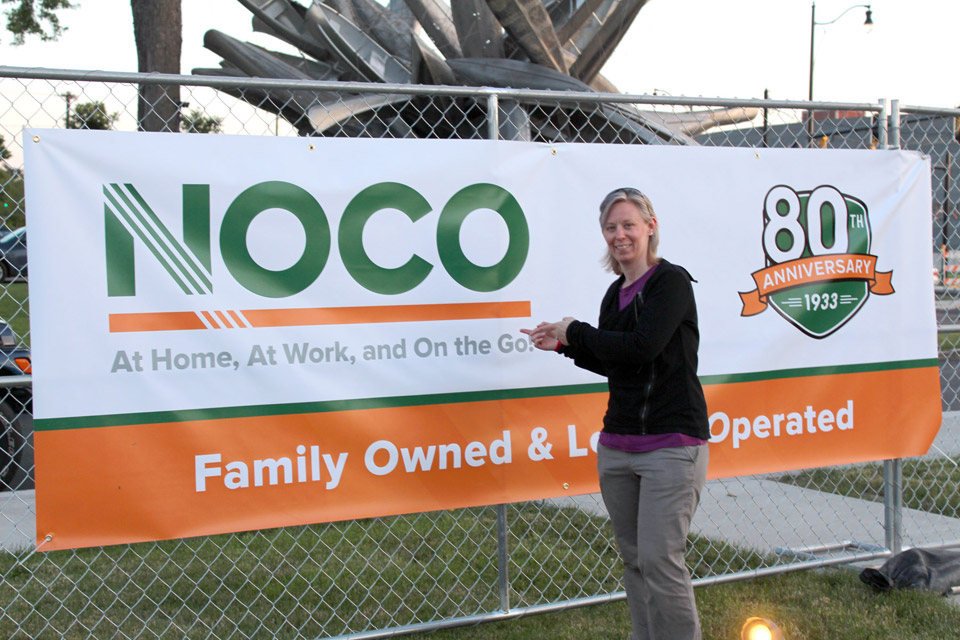 Kristin next the the NOCO banner at the POParazzi event